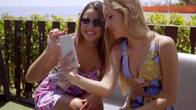 Two young women checking out a mobile phone stock footage