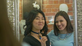Two young women checking their look and discussing new purchases in jewerly store stock footage