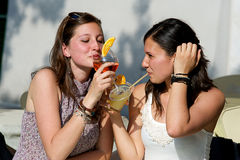 Two Young Women Cheering with Cold Drinks Royalty Free Stock Images