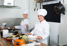 Two young women chefs cooking food at kitchen Stock Photo