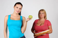 Two young women choosing food for diet Royalty Free Stock Photos