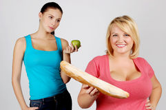 Two young women choosing food for diet Stock Photos