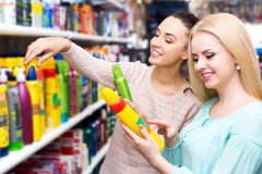 Two young women choosing hair styiling mousse Royalty Free Stock Photo