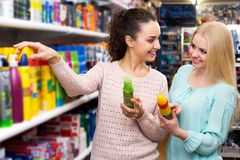 Two young women choosing hair styiling mousse Stock Photos