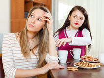 Two young women after conflict. At table in home Stock Image