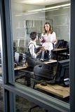Two young women conversing in computer lab. Young women, librarians, teachers or university students conversing in computer room, reflection of library book Stock Photo