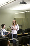 Two young women conversing in computer lab. Two young women, office workers or university students, conversing in computer room Stock Images