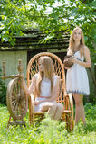 Two young women in country yard with spinning wheel and rock chair royalty free stock image