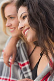 Two young women covered with blanket at beach Stock Photography