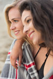 Two young women covered with blanket at beach Stock Photo