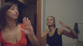 Two young women are dancing in the kitchen at home. Slow motion stock video footage