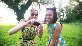 Two young women dancing and taking selfies. Two beautiful young women dancing together and having fun while taking selfies in the park stock video