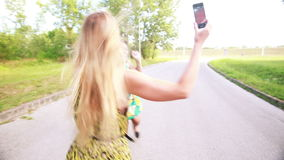 Two young women dancing and taking selfies. Two beautiful young women dancing together and having fun while taking selfies in the park stock video footage