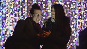 Two Young Women with Dark Hair Laughing Looking at Smartphone Screen on Christmas Lights Background. Smiling Girls Use stock video