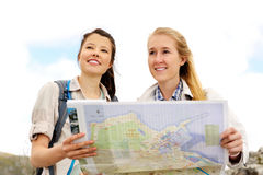 Two young women discussing the direction to take. Two cheerful women hiking outdoors and consulting their map for the direction in which to travel royalty free stock photography