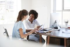 Two young women discussing documents at a desk in an office stock photo