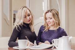 Two young women at meeting in conference room stock photos