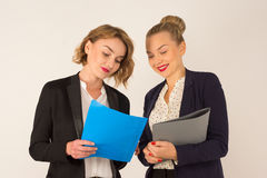 Two young women discussing documents. On a white background Royalty Free Stock Photos