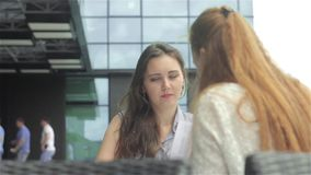 Two young women discussing the problems with documents in outdoor cafe. Shooting from the back of girl. Two beautiful young women sitting in outdoor cafe near stock footage
