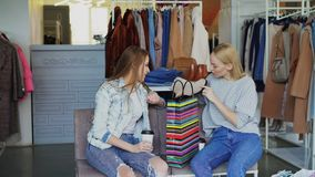 Young women discussing purchased ankle shoes while having rest in boutique. Girls are excited about shopping, gestiuring. Two young women discussing purchased stock footage