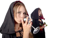 Two young women in disguise halloween with a glass of blood and Stock Photos
