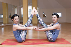 Two young women do yoga Royalty Free Stock Images