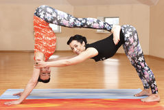 Two young women do yoga Stock Image