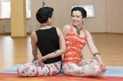 Two young women do yoga Stock Photos