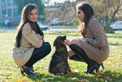 Two Young Women with a dog in the autumn park Royalty Free Stock Image