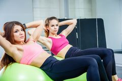Two young women doing abdominal exercises using the gymnastic ball in a gym. Royalty Free Stock Photo