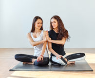 Two young women doing namaste in lotus pose at a fitness studio Royalty Free Stock Photography