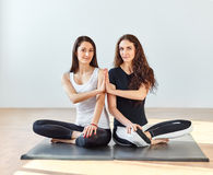 Two young women doing namaste in lotus pose at a fitness studio Stock Image