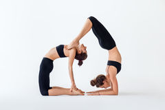 Two young women doing partner yoga asana camel pose and scorpion Royalty Free Stock Photos