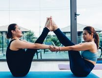 Two young woman doing pose yoga pull arm together royalty free stock photos