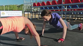 Two young women doing push-ups. And clapping hands stock video footage