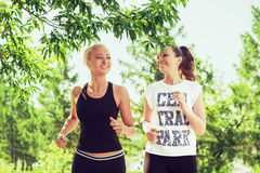 Two young women doing sports outdoors in a park on sunny summer. Day. Girls running in sportswear Stock Images