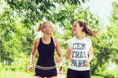 Two young women doing sports outdoors in a park on sunny summer. Day. Girls running in sportswear Royalty Free Stock Photos