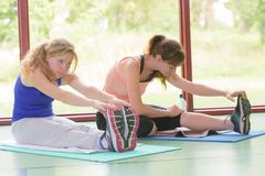 Two young women doing stretching in fitness room Stock Images