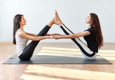 Two young women doing yoga asana buddy boat pose Stock Images