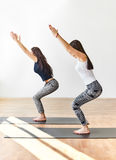 Two young women doing yoga asana chair pose Stock Images