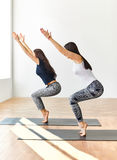 Two young women doing yoga asana chair pose Stock Photography
