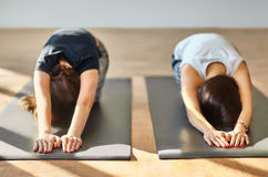 Two young women doing yoga asana child's pose Stock Photos