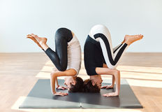 Two young women doing yoga asana crane pose Royalty Free Stock Photos