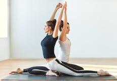 Two young women doing yoga asana Eka Pada Rajakapotasana. One le Stock Images