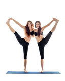 Two young women doing yoga asana extended hand to big toe pose. Utthita Hasta Padangustasana. Isolated on white background Royalty Free Stock Images