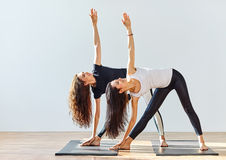 Two young women doing yoga asana extended triangle pose. Trikonasana Stock Photos