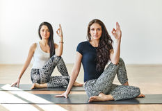 Two young women doing yoga asana half lord of the fishes pose Royalty Free Stock Photos