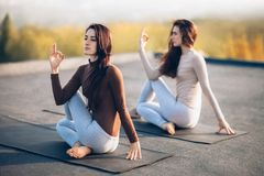 Two young women doing yoga asana half lord of the fishes pose. On the roof outdoor. Ardha Matsyendrasana Stock Photos