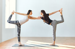 Two young women doing yoga asana lord of the dance pose Royalty Free Stock Photo