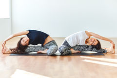 Two young women doing yoga asana revolved head to knee pose Royalty Free Stock Photography
